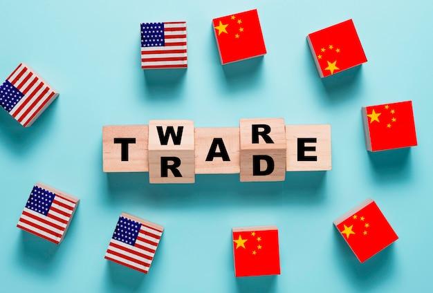 Handelskriegsformulierung auf holzwürfelblock mit usa- und china-flagge. es ist symbol des wirtschaftlichen zollhandelshandelskriegs und der steuerbarriere zwischen den vereinigten staaten von amerika und china. Premium Fotos