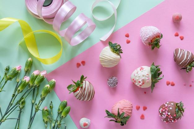 Handgemachte erdbeeren, blumen und dekoration mit schokoladenüberzug zum kochen des desserts auf farbigem hintergrund Premium Fotos