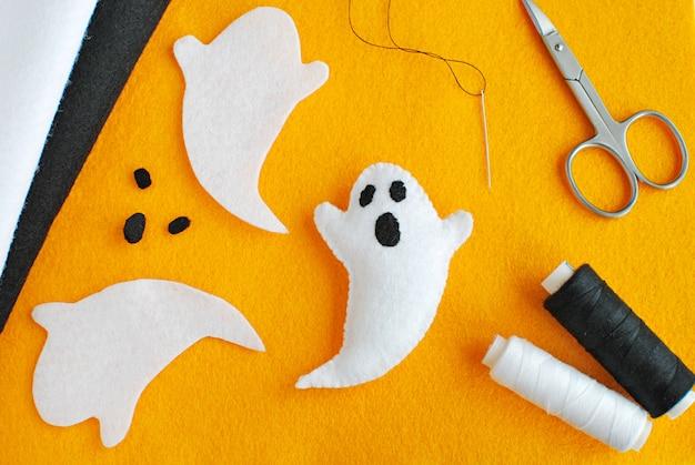 Handgemachte halloween-deko aus filzstoff, anleitung zur herstellung von filzgeistern. Premium Fotos