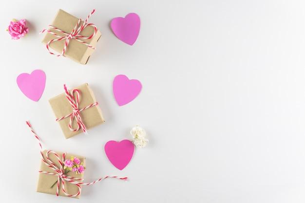 Handgemachte rosa liebesherzen und geschenkbox lokalisiert auf weißem hölzernem hintergrund Premium Fotos