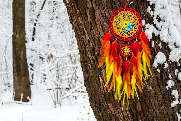 Handgemachter traumfänger mit federn auf einer winterlandschaft Premium Fotos