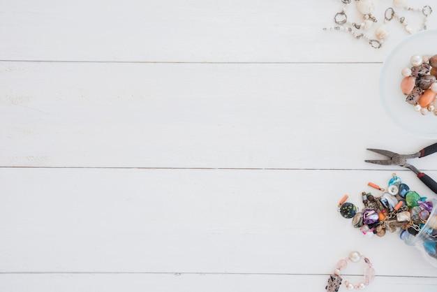 Handgemachtes armband und zangen auf weißem hölzernem schreibtisch Kostenlose Fotos