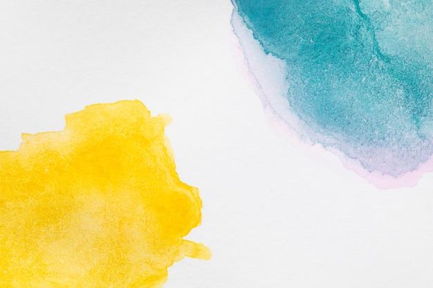 Handgemalte flecken der gelben und blauen farbtöne Kostenlose Fotos