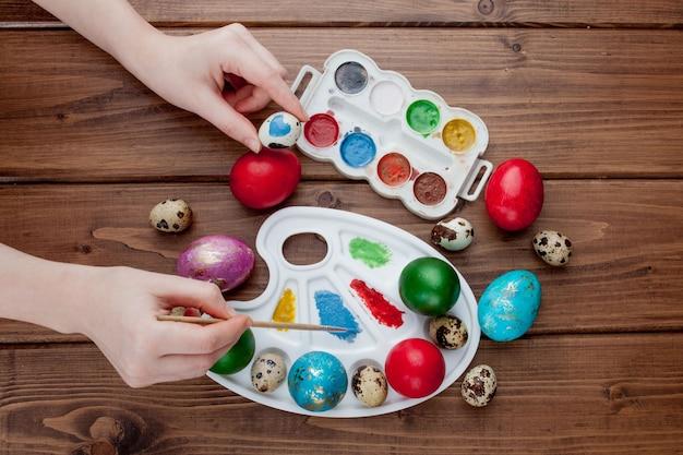 Handgemalte ostereier, farben und pinsel auf hölzernem hintergrund. vorbereitung auf den urlaub. mädchenhände zeichnen ein muster Premium Fotos