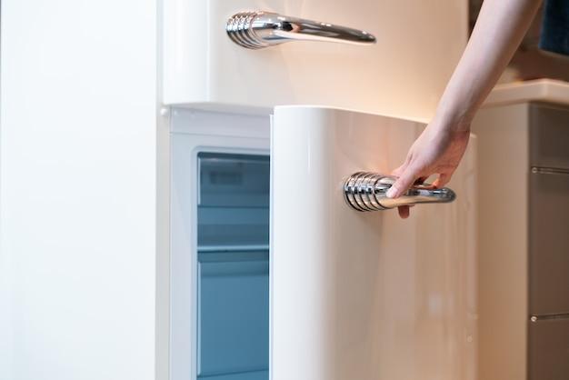 Handgeöffnete kühlschranktür in der küche Premium Fotos