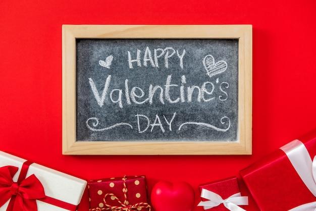 Handgeschriebener text des glücklichen valentinstags auf tafel mit geschenkbox Premium Fotos