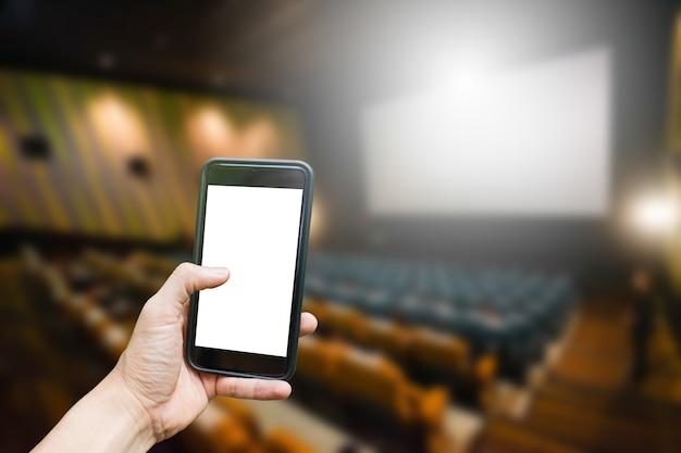 Handgriff auf mobile mit kinohintergrund Premium Fotos
