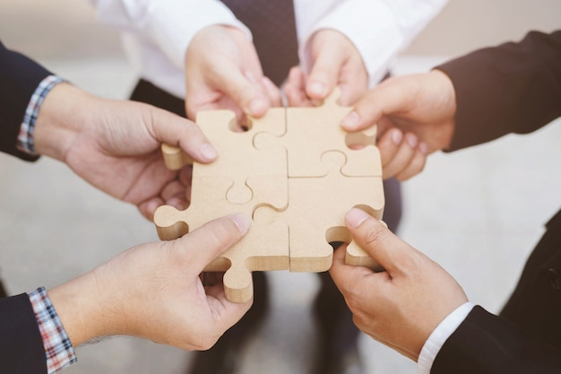 Handgriff mit drei geschäftsmännern, der versucht, hölzernes puzzlestück des puzzlen anzuschließen. ein teil des ganzen. symbol der assoziation und verbindung. erfolgs- und geschäftslösungsstrategie Premium Fotos