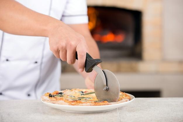 Handkoch bereitet eine pizza am kithen zu. Premium Fotos