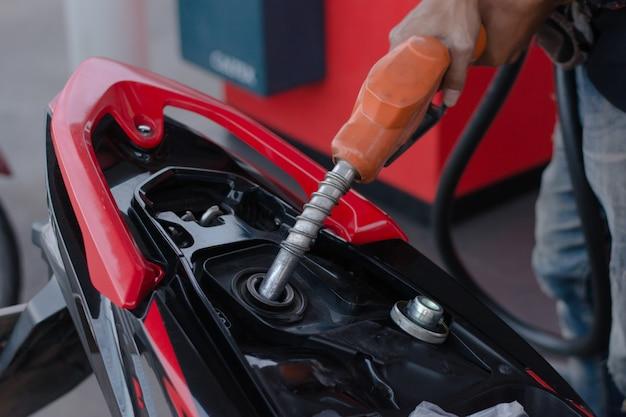 Handkraftstoffdüse beim gießen zum motorrad an der tankstelle Premium Fotos
