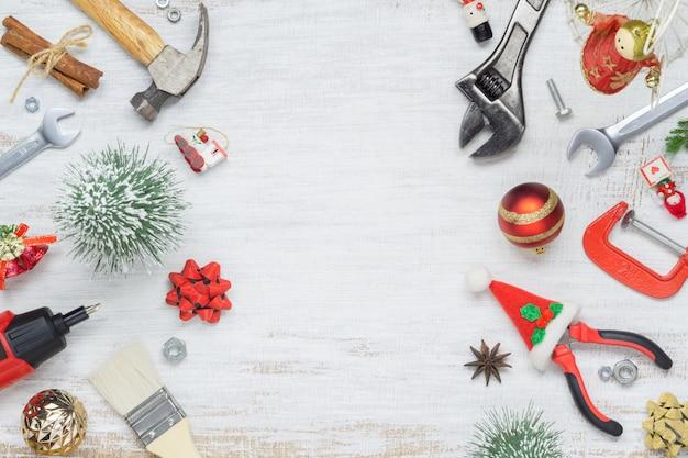 Handliche werkzeuge des baus mit weihnachtsverzierung auf weißem holz Premium Fotos