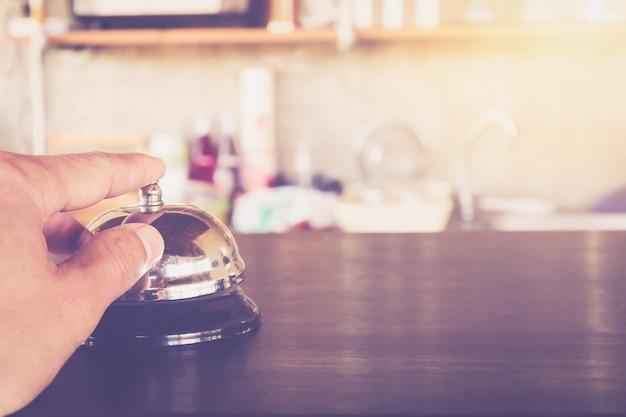 Handpressen eines service bell-anrufservice auf kaffeecafé oder restaurant counter close up Premium Fotos