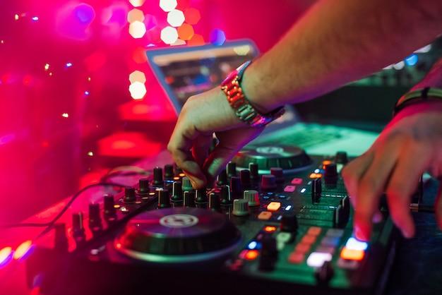 Hands dj mischt und spielt musik auf einem professionellen controller-mixer Premium Fotos