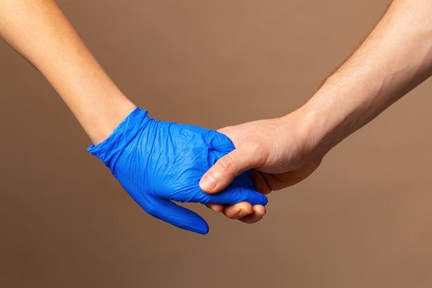 Handschlag in blauen handschuhen, hilfekonzept. Premium Fotos