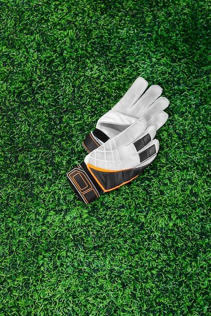 Handschuhe des torhüters auf einem grünen rasen Premium Fotos