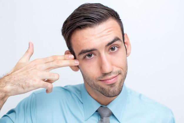 Handsome manager schießt sich mit fingern Kostenlose Fotos