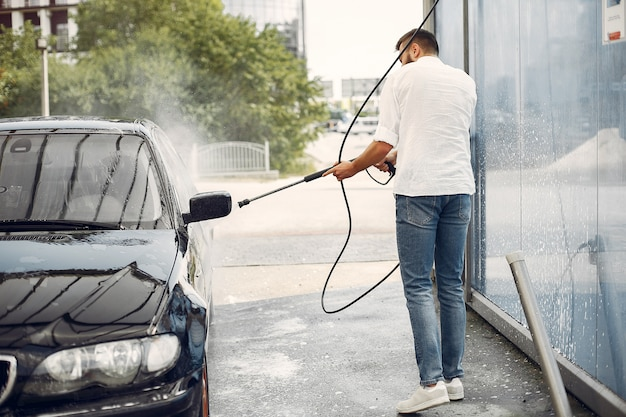 Handsomen mann in einem weißen hemd, das sein auto wäscht Kostenlose Fotos