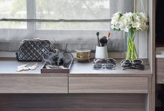 Handtasche, sonnenbrille, schmuck und make-upbürsten auf einer hölzernen frisierkommode Premium Fotos