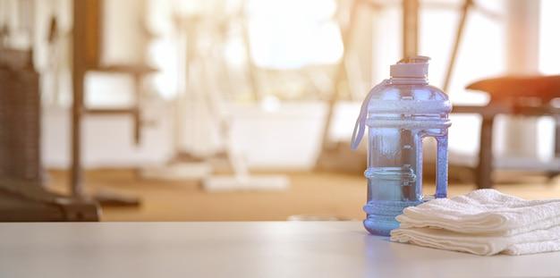 Handtücher und sportflasche mit textfreiraum in der turnhalle Premium Fotos