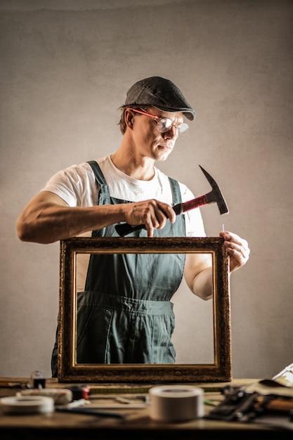 Handwerker, der einen rahmen repariert Premium Fotos