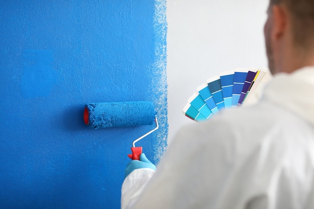 Handwerker hält walze und eine farbpalette und malt weiße wand blau. wandmalerei und malkonzept Premium Fotos
