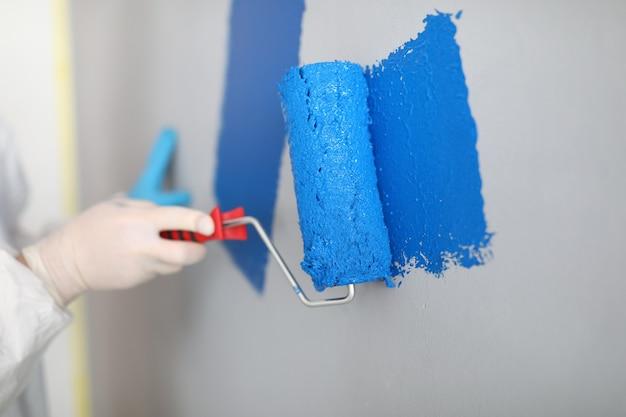 Handwerker hält walze und malt weiße wand blau. maler-service-konzept Premium Fotos