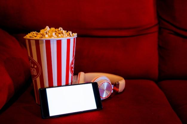 Handy mit leerem weißem hellem schirm mit popcorneimer auf dem roten sofa Premium Fotos