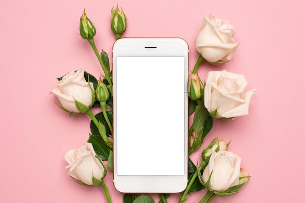 Handy mit rosen blüht auf rosa pastellhintergrund, frauentechnologiekonzept Premium Fotos