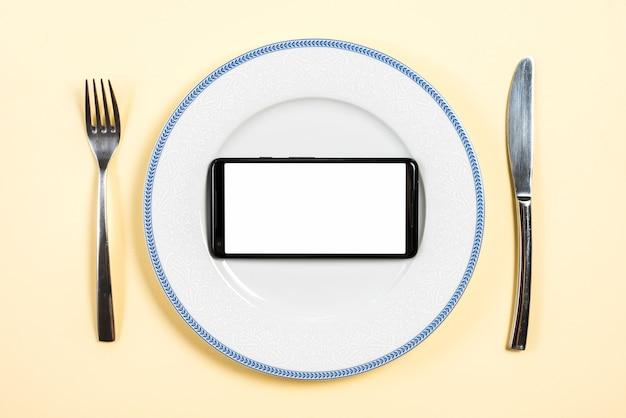 Handy mit weißer bildschirmanzeige auf platte mit gabel und buttermesser gegen beige hintergrund Kostenlose Fotos