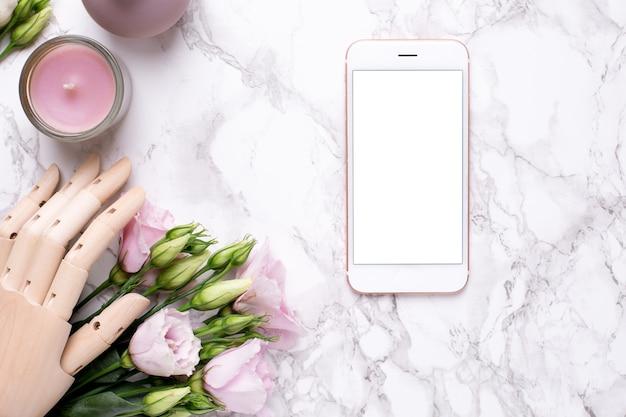 Handy und hölzerne hand mit rosa blumen auf marmor Premium Fotos