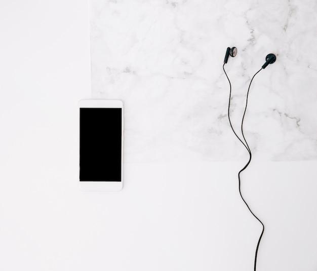 Handy und kopfhörer auf weißem strukturiertem hintergrund Kostenlose Fotos