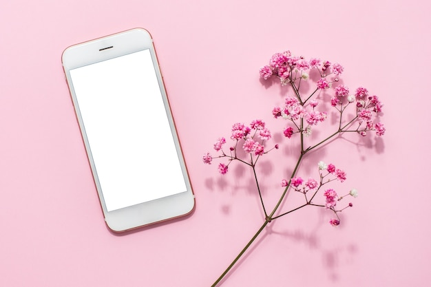 Handy und rosa blumen auf rosa pastelltisch Premium Fotos