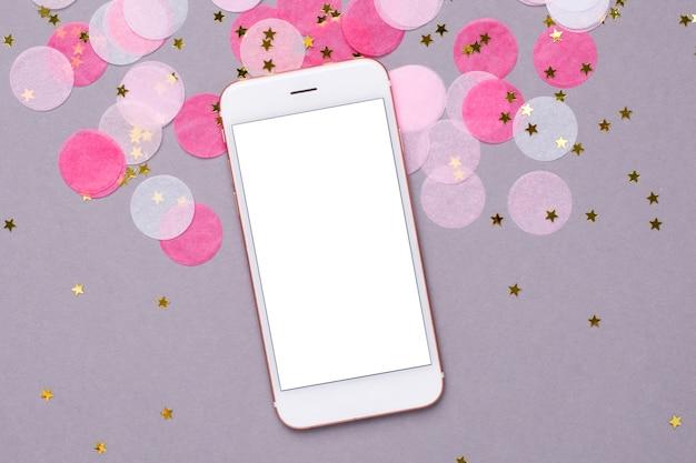 Handy und rosa konfettis mit goldsternen auf grau Premium Fotos