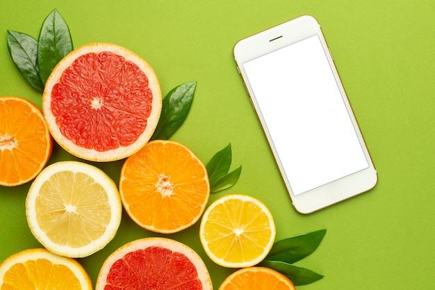 Handy und zitrusfrüchte, technologie und obst flatlay, sommerliche minimalkomposition mit grapefruit, zitrone, mandarine und orange Premium Fotos