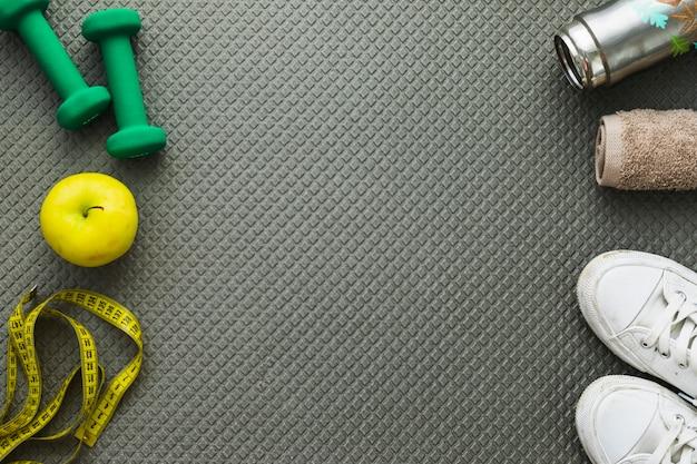Hanteln; apfel; maßband; sportschuhe; handtuch und wasserflasche auf trainingsmatte Kostenlose Fotos