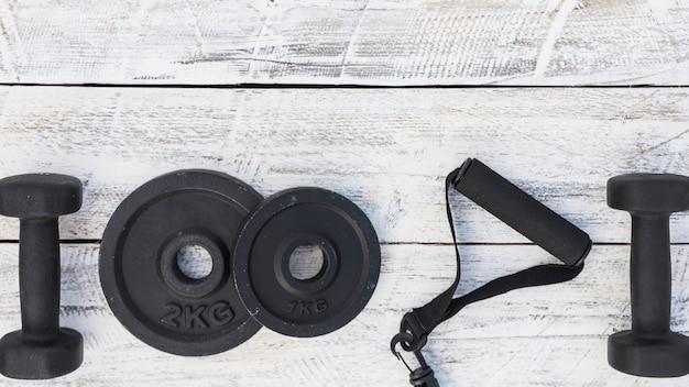 Hanteln; gewichtsplatten und eignungsbügel auf weißem hölzernem strukturiertem hintergrund Kostenlose Fotos