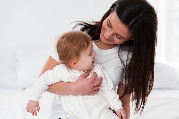 Happy baby von mutter im bett gehalten Kostenlose Fotos
