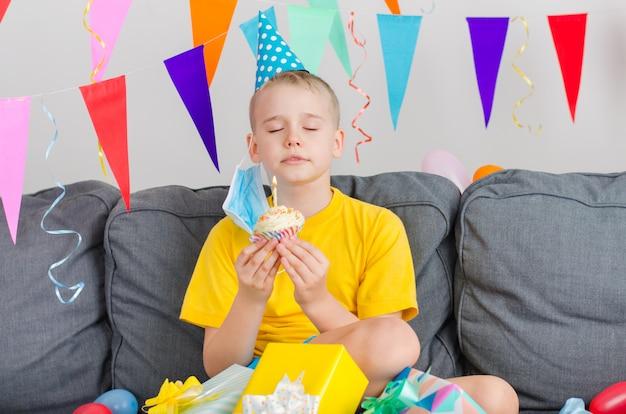 Happy boy nahm seine gesichtsmaske ab und hielt urlaub cupcake macht wunsch Premium Fotos