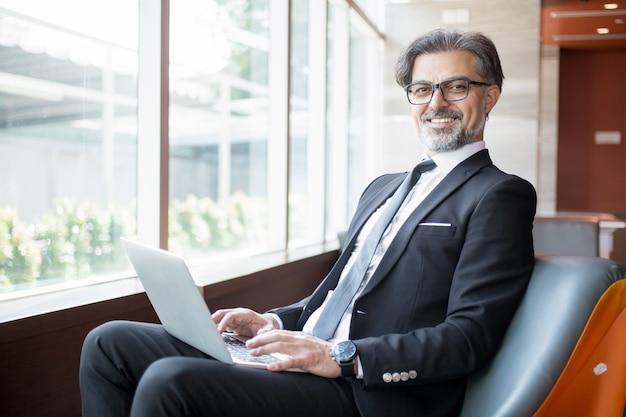 Happy business leader mit tablet in der lobby Kostenlose Fotos