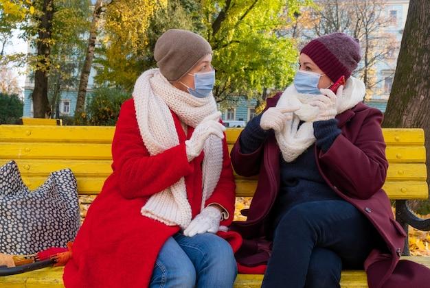 Happy couple senioren oder frauen mittleren alters tragen eine medizinische schutzmaske und sitzen auf einer bank im herbstpark. Premium Fotos