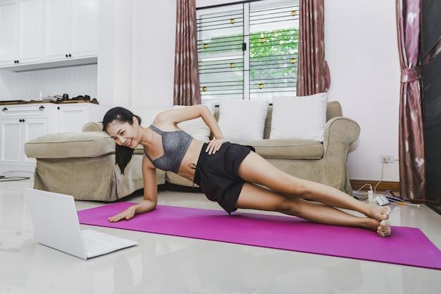 Happy fit asiatische frau training fitness-übung online mit laptop zu hause Premium Fotos