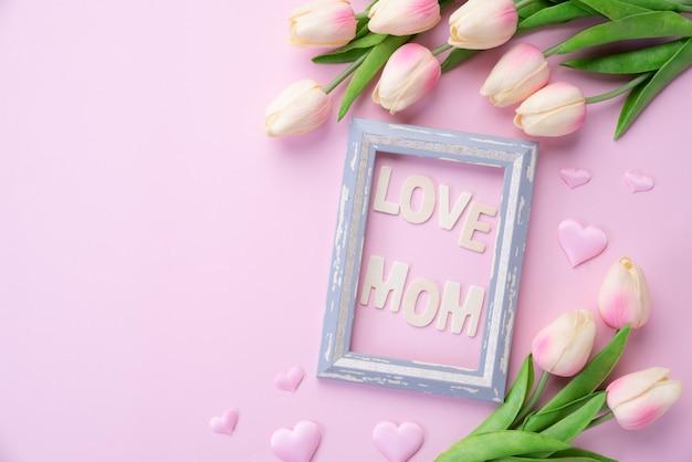Happy muttertag konzept. rosa tulpenblume mit papierherzen und bilderrahmen Premium Fotos