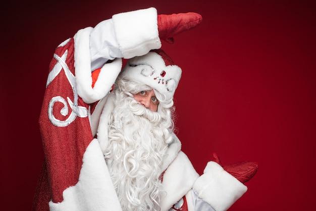 Happy santa claus zeigt größe oder dimension von hand in handschuhen Kostenlose Fotos