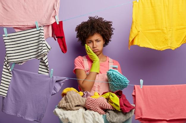Hart arbeitende müde hausfrau seufzt vor müdigkeit, berührt die wange, trägt gummihandschuhe, steht in der nähe von wäscheleinen mit aufgehängter sauberer kleidung, langweilt sich vom alltag zu hause, wäscht den ganzen tag Kostenlose Fotos