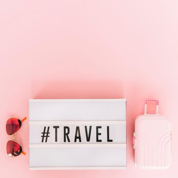 Hashtag mit reisetext auf lightbox mit sonnenbrille und miniaturreisetasche auf rosa hintergrund Kostenlose Fotos