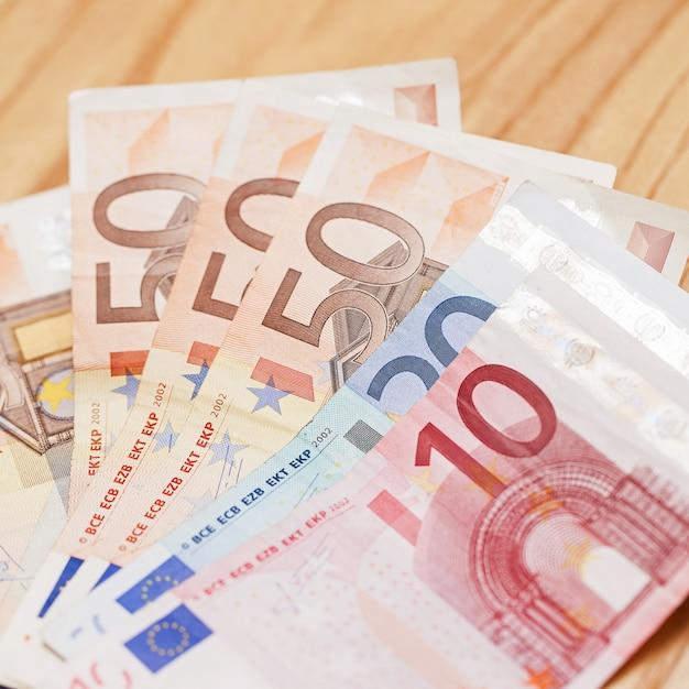 Haufen von eurobanknoten auf einem holztisch Kostenlose Fotos