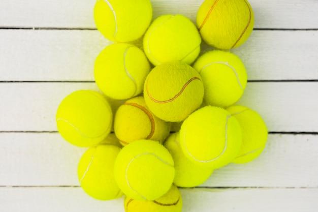 Haufen von grünen tennisbällen auf holztisch Kostenlose Fotos