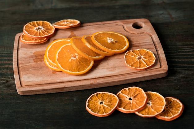 Haufen von scheiben frischer und trockener orangen auf rechteckigem holzschneidebrett auf dunklem tisch, der als wand verwendet werden kann Premium Fotos