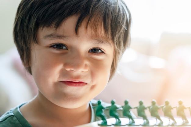 Hauptschuß des glücklichen kinderjungen kamera mit lächelndem gesicht betrachtend Premium Fotos