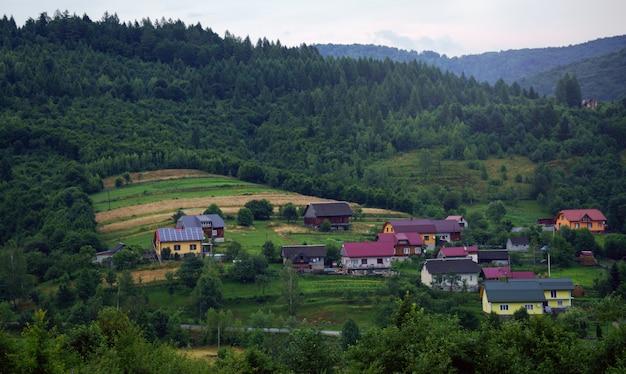 Haus mit sonnenkollektoren auf dem land der ukraine - blick auf häuser in einem kleinen dorf im berg Premium Fotos